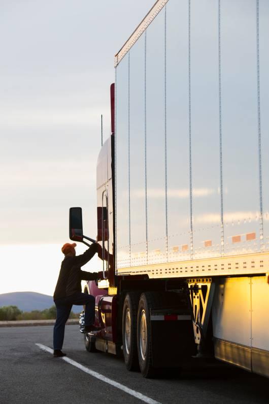 Chauffeur routier montant dans son camion en direction d'un entrepôt logistique